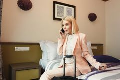 Happy business woman sitting in hotel room Stock Image