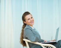 Happy business woman sitting with laptop Royalty Free Stock Image