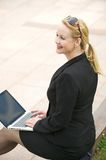 Happy business woman sitting outdoors with laptop Royalty Free Stock Photography