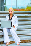 Happy business woman sitting on stairs at office Stock Photos