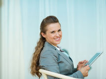 Happy business woman sitting with tablet PC Stock Image