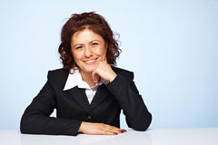 A happy business woman smiling. Image of a happy business woman smiling against blue background Royalty Free Stock Image