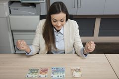 Happy business woman spreads money on a desk Royalty Free Stock Photography