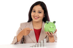 Happy business woman with stack of coins and piggy bank Royalty Free Stock Photography
