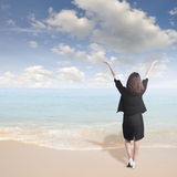 Happy business woman standing on beach and sun sky Stock Photo