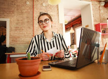 Happy business woman at the table with laptop in office. Happy business woman at the table with a laptop in the office Stock Photography
