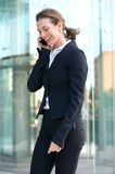 Happy business woman talking on cell phone outside Stock Images