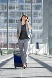 Happy business woman talking on mobile phone at airport Royalty Free Stock Photography