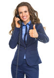 Happy business woman talking phone and showing thumbs up Royalty Free Stock Image