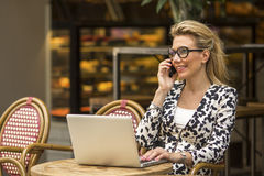 Happy business woman talking on the phone and using laptop computer in a coffee shop Royalty Free Stock Photo