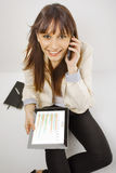 Happy business woman talking on smart phone and working on digital tablet Royalty Free Stock Photo