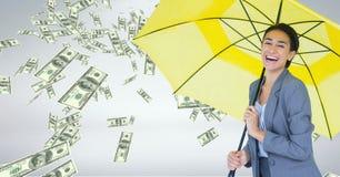 Happy business woman under umbrella with money rain against grey background