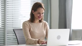 Happy business woman using computer communicating online sitting at desk