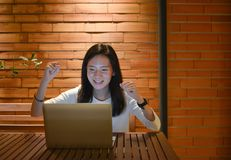 Happy business woman using a laptop and working at night royalty free stock photography