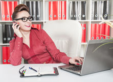 Happy business woman using mobile phone and working with laptop Stock Photo