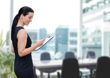 Happy business woman using a phone against office background Royalty Free Stock Photos