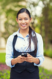 Happy business woman using smart phone. Portrait young, beautiful, smiling woman lawyer holding mobile smartphone. Multiethnic female professional in the city Royalty Free Stock Photos