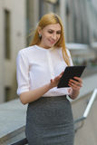Happy business woman using tablet pc in front of office building Royalty Free Stock Photo