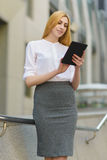 Happy business woman using tablet pc in front of office building Stock Images