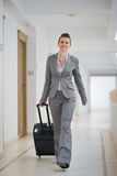 Happy business woman walking with bag on wheels Stock Images