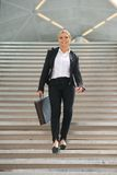 Happy business woman walking downstairs with briefcase Royalty Free Stock Photo
