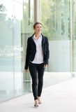 Happy business woman walking outside office building Royalty Free Stock Image