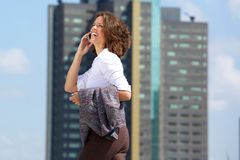 Happy business woman walking and talking on cell phone Stock Image