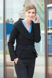 Happy business woman walking and talking on mobile phone outdoors Stock Photo