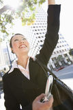 Happy Business Woman Waving Hand. Low angle view of happy businesswoman waving hand with building in the background Stock Images