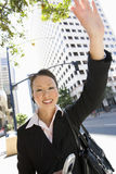 Happy Business Woman Waving Hand. Portrait of happy business woman waving hand with building in the background Royalty Free Stock Photography