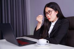 Happy business woman working on laptop computer and drinking a c. Happy young business woman working on laptop computer and drinking a cup of coffee Royalty Free Stock Photos