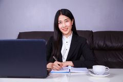 Happy business woman working with laptop computer and writes a j. Happy young business woman working with laptop computer and writes a journal on the notebook Royalty Free Stock Photography