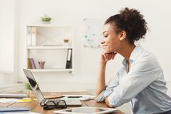 Happy business woman working on laptop at office. Happy smiling african-american business woman working on laptop at office. Businesswoman sitting at her working Stock Image