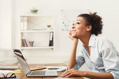 Happy business woman working on laptop at office. Happy thoughtful business woman working on laptop at office. Businesswoman sitting at her working place, copy Stock Photos