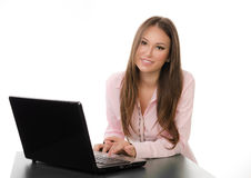 Happy business woman working on a laptop. Smiling blonde business woman working on a laptop at her desk, studio shot over white background Royalty Free Stock Photos