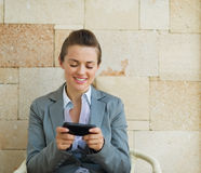 Happy business woman writing text message Stock Photo