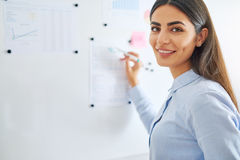 Happy business woman writing on white board Stock Photography