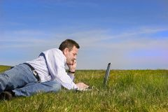 Happy businessman. Businessman laying on the grass with his lap, looking aside stock photography