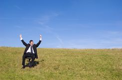 Happy businessman. Young businessman sitting on a chair on the meadow stock image