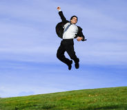 Happy businessman. Successful and happy young adult businessman running and jumping in the green field Royalty Free Stock Photos