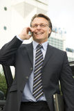 Happy businessman. A handsome forties businessman enjoys a lighthearted conversation on his cellphone whilst holding his laptop computer Stock Images