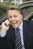 Happy businessman. A handsome forties businessman enjoys a lighthearted conversation on his cellphone whilst sitting in his car Stock Photography