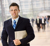 Happy businessman. Portrait of happy successful businessman holding newspaper, smiling Royalty Free Stock Photo