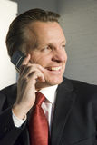 Happy businessman. A happy forties businessman gives a stunning smile as he enjoys a lighthearted conversation on his cellphone Royalty Free Stock Photography