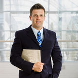 Happy businessman. Portrait of happy successful businessman holding newspaper, smiling Stock Photography