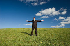 Happy businessman. Happy business man standing on green grass - arms outstretched Royalty Free Stock Photography