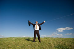Happy businessman. Happy business man standing on green grass - arms outstretched Royalty Free Stock Photos