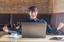 Happy businessman achiving his goal and showing fists  with laptop Royalty Free Stock Images