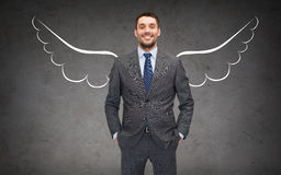Happy businessman with angel wings over gray Royalty Free Stock Images