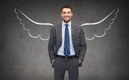 Happy businessman with angel wings over gray Royalty Free Stock Photography